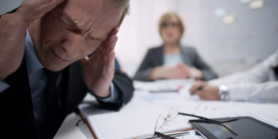 Male worker has migraine attack caused by stress and exhaustion